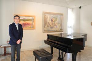館長の濱崎庄一さんと世良臣絵の油彩画。ピアノがある1階ではコンサートが開かれることも
