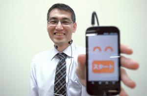 板村英典さん プロジェクトaH理事。関西大学でコミュニケーションを研究後、同団体で笑いの研究について取り組む。手にしているのは笑い声測定システム「アッハ・メーター」
