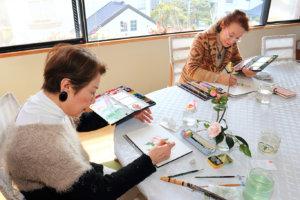 水彩画倶楽部の安井富子さん=左=と須藤佳子さん。「写真ではなく、実物をしっかりと観察して描くのが世良流です」
